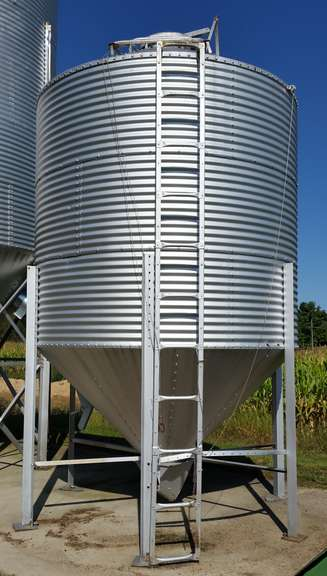 Brock Grain / Feed Bin, 9' Dia. With 3-Rings (Total Length is 16'), Approx. 500-Bushel Bin, Grain Bagger Installed on Bin Cone, Bin is Fully Assembled and Down Ready for Loading, Seller Can Assist Buyer with Loading Bin on Trailer, Good Condition
